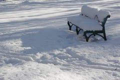 Snö-täckt bänk i en solig vinterdag   Arkivbild