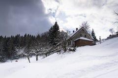 Snö täckte huset i ett frostigt bergland i solig dag Arkivfoto