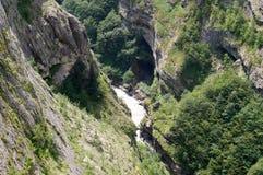 Snabb flod för rengöring som omges av berg, landskap på en solig dag Arkivfoton