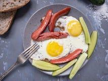 Snabb frukost av förvanskade ägg med korvar royaltyfri bild