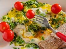 Snabb frukostomelett med gräsplaner, körsbärsröda tomater, brödkorn Arkivbilder