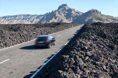 Snabb körning för bil på rutten TF-38 i mitt av vulkaniska lavakiselstenar på asfaltvägen Kanariefågel Tenerife Royaltyfri Bild