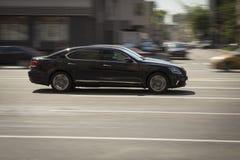 Snabb körning för svart bil på en stadsgata Arkivfoto