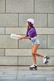 Snabb leverans av den sportive flickan på rullskridskor Arkivbild