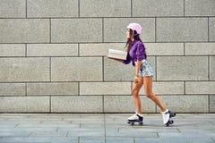 Snabb leverans av den sportive flickan på rullskridskor royaltyfri bild