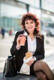 Snabb lunch - affärskvinna som äter i gata Royaltyfri Foto