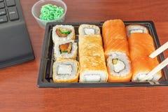 Snabb lunch på arbete - brist av tid ut ur kontoret Sushirullar med wasabi på arbetsplatsen royaltyfri bild