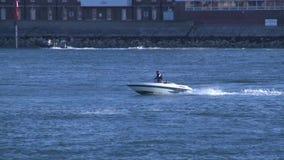 Snabb motorbåt som kryssar omkring till och med den Portsmouth hamnen arkivfilmer
