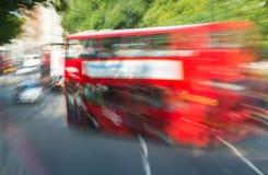 Snabb rörande röd buss i London som inramas av träd Royaltyfria Foton