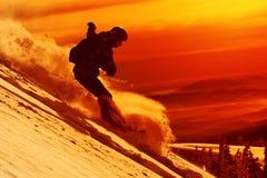 Snabb snowboarder som är sluttande i pulver Arkivfoto