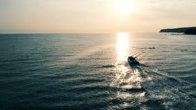 Snabba motorbåten svävar över öppet vatten på en solnedgång stock video
