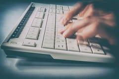 Snabba skriva fingrar på ett datortangentbord arkivbilder