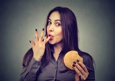 Snabbmat är min favorit Kvinna som äter en hamburgare som tycker om smaken Arkivfoto