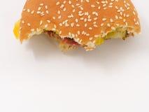 Snabbmat biten hamburgare på vit bakgrund arkivbild