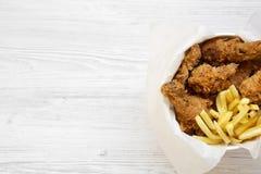 Snabbmat: stekt kycklingtrumpinnar, kryddiga vingar, pommes frites och anbudremsor i pappers- ask över vit träyttersida, sikt frå fotografering för bildbyråer