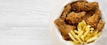 Snabbmat: stekt kycklingtrumpinnar, kryddiga vingar, pommes frites och fega remsor i pappersask över vit träyttersida, bästa sikt royaltyfria bilder