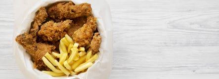 Snabbmat: stekt kycklingtrumpinnar, kryddiga vingar, pommes frites och mjuka remsor i pappersask över vit träyttersida, uppe i lu royaltyfria foton