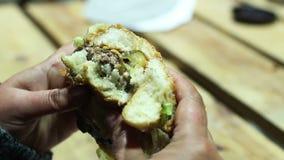 Snabbmatknarkare som biter den äckliga fetthaltiga hamburgaren, kalorier och genomdränkt fett arkivfilmer