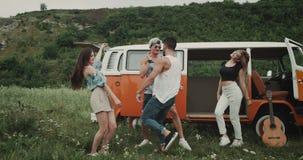 Snabbt dansa gruppen av unga vänner på naturen, flytta sig som är karismatiskt, bredvid en retro skåpbil arkivfilmer