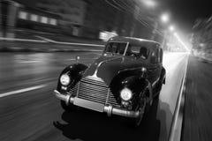 Snabbt drev för gammal retro bil på asfaltstadsvägen på natten arkivbild