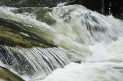 snabbt flöda över rocksvatten Arkivfoton