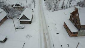 Snabbt flyg över en väg i Carpathian by Fågels sikt för öga av snö-täckte hus lantlig vinter för liggande lager videofilmer