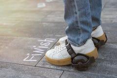 Snabbt fullföljande Foten skor i hjulet framme av ordfullföljandet Fotografering för Bildbyråer
