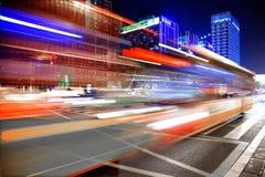 Snabbt och suddigt bussa ljusa slingor i i stadens centrum nightscape Arkivbild