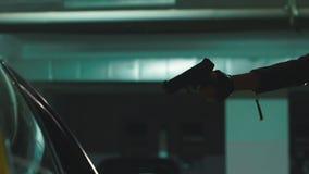 Snabbt syfte för faramördarekvinna med vapnet på offret i bil i källaren arkivfilmer