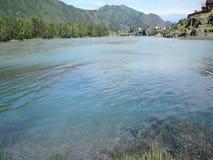 Snabbt vattenflöde i bergfloden med den lilla byn i bakgrund lager videofilmer