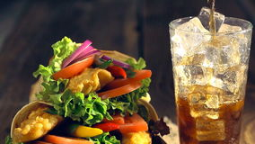 Snach wrap with chicken and vegetables served with cold drink stock video footage