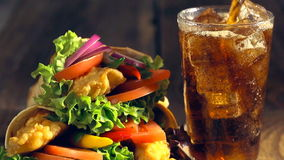 Snach wrap with chicken and vegetables served with cold drink stock footage
