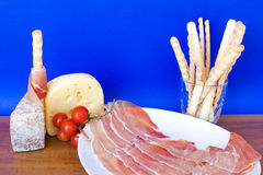 Snack. Food & Drinks -  italian appetizers: ham, cheese, bread-sticks and cherry tomatoes Royalty Free Stock Images