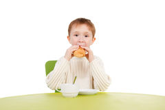 Snack. Closeup image of the handsome little boy eating a snack near the table Stock Image