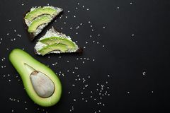 Snack avocado on dark rye bread with fresh sliced avocado and cream cheese top. Copy space stock image