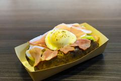 Snack of baked potatoes, bacon and poached eggs in a carton box on a black table royalty free stock images