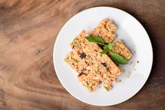 Snack bar or energy bar. On white dish and wooden background, top view Royalty Free Stock Photos