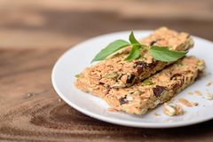 Snack bar or energy bar. On white dish and wooden background Stock Photography