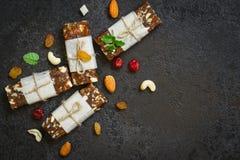 Snack bar sani dei frutti secchi e dadi su fondo concreto nero Fotografie Stock