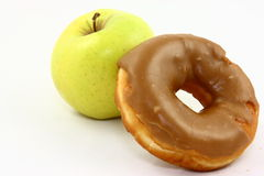 Snack Battle -Healthy vs Unhealthy. A yellow apple and a glazed doughnut photographed on a white background Royalty Free Stock Photos