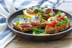 Snack of bread, soft cheese and pickled herring. Royalty Free Stock Image