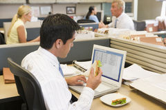 Snack break at office. A young man working at a laptop computer in an office, having a sandwich break Stock Image
