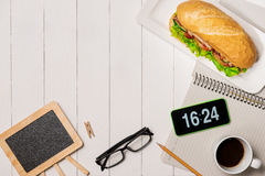 Snack at break time. Healthy business lunch in office, top view. Of Vietnamese sandwich, or Ban Mi on white wooden desk with coffee, mobile phone and notepad Stock Image