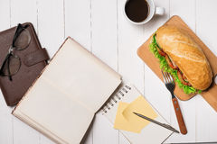 Snack at break time. Healthy business lunch in office, top view. Of Vietnamese sandwich, or Ban Mi on white wooden desk with coffee, mobile phone and notepad Stock Photos