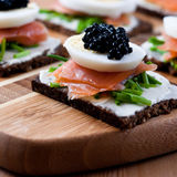 Snack with caviar and salmon. Canapes with egg,caviar and smoked salmon Stock Image