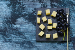 Snack cheese with fruit. On a black board Royalty Free Stock Images