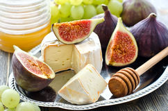 Snack with cheese, honey and fruits, figs and grapes. On silver tray wooden background Stock Photography