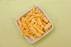 Snack corn cheese in square bowl on green top Royalty Free Stock Photo
