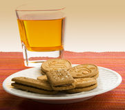 Snack of Cream filled Cookies and Fruit Juice. Photo Showing Cream Filled Cookies and a Glass of Fruit Juice on a Tablecloth stock photo