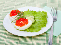 Snack of eggs with red salmon caviar Royalty Free Stock Image